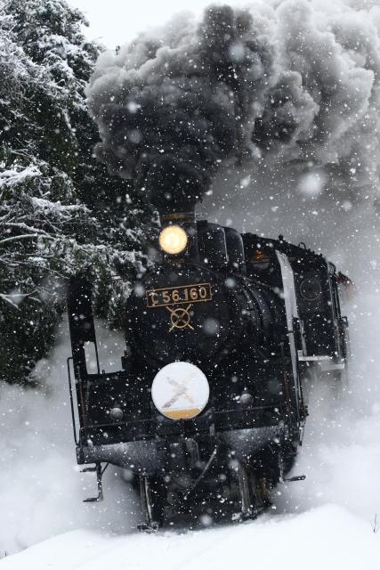 雪の中を走る蒸気機関車の写真